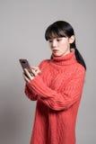 Studiostående av den asiatiska kvinnan för tjugotal som mottar en okänd appell Royaltyfria Bilder