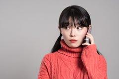 Studiostående av den asiatiska kvinnan för tjugotal som mottar en okänd appell Arkivfoto