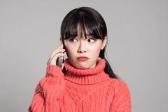 Studiostående av den asiatiska kvinnan för tjugotal som mottar en okänd appell Arkivfoton