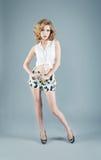 Studiostående av den blonda kvinnan i kortslutningar och den vita blusen Sexigt Fotografering för Bildbyråer
