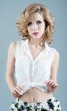 Studiostående av den blonda kvinnan i kortslutningar och den vita blusen Sexigt Royaltyfri Bild