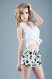 Studiostående av den blonda kvinnan i kortslutningar och den vita blusen Sexigt Royaltyfria Bilder