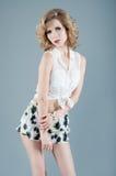 Studiostående av den blonda kvinnan i kortslutningar och den vita blusen Sexigt Royaltyfria Foton