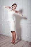 Studiostående av den eleganta kvinnan i den vita coctailklänningen Arkivfoton