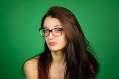 Studiostående av den gulliga smarta flickan i glasögon och den röda överkanten på grön bakgrund royaltyfri foto