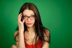 Studiostående av den gulliga smarta flickan i glasögon och den röda överkanten på grön bakgrund Strikt sexig blick till och med e arkivfoton