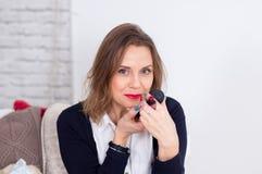 Studiostående av den sinnliga unga affärskvinnan med blont hår och sexiga fulla kanter som sätter röd läppstift som lite rymmer royaltyfri fotografi