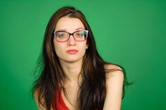 Studiostående av den smarta brunettkvinnan i glasögon och röd skjorta på grön bakgrund fotografering för bildbyråer