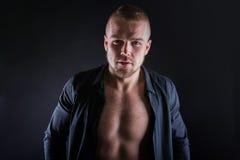 Studiostående av den stiliga sexiga sportiga unga mannen Muskulös man med den nakna torson som bär den svarta skjortan Royaltyfria Foton