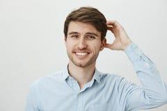 Studiostående av den tvekande förbryllade attraktiva europeiska grabben med att skrapa för skägg som är head, och att le med nerv arkivbild