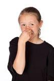 Studiostående av en flicka som rymmer hennes näsa isolerad på vit Royaltyfri Fotografi