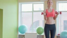 Studiostående av en härlig sportig muskulös kvinna som utarbetar med två hantlar stock video