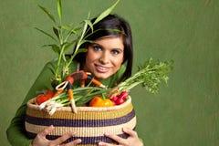 Studiostående av en kvinna med en korg som är full av grönsaker Royaltyfri Bild