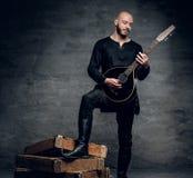 Studiostående av en man i traditionell keltisk kläder som spelar på mandolinen royaltyfri fotografi
