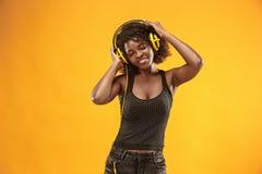 Studiostående av lyckligt le för förtjusande lockig flicka under photoshoot Bedöva den afrikanska kvinnan med ljus-brunt hud fotografering för bildbyråer