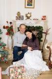 Studiostående av par med ålderskillnaden som sitter nära den konstgjorda spisen och julgranen med gåvaaskar och royaltyfria foton