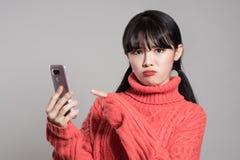 Studioståenden av asiatiska kvinnor för tjugotal förargade vid telefonen Arkivfoto