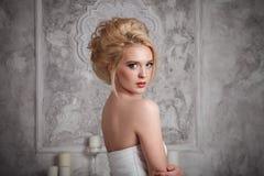 Studiostående av den härliga unga bruden i den vita klänningen Royaltyfri Bild