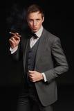 Studiostående av den unga mannen som röker en cigarr Arkivbild
