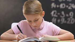 Studious pupil writing test work, school lessons, math equation on blackboard. Stock footage stock video