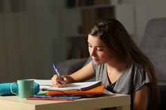 Studious student doing homework late hours in the night. At home Stock Image