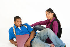Studious Teen Couple. Studious, attractive teen couple wearing backpacks and holding books lying on the ground stock photo