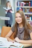 Młoda studencka dziewczyna pracuje z książką w bibliotece Zdjęcia Stock