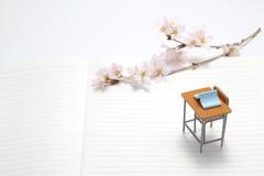 Studiuje biurko, błękitną książkę i czereśniowych okwitnięcia, zdjęcia royalty free
