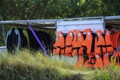 Studland, Dorset, England - June 01 2018: Racks of orange life j. Ackets or life vests, and wetsuits ackets or life vests, and wetsuits stock photos