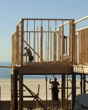 Studs by the sea. New house construction at the beach with two workers Stock Image