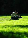 Study. Female Student studying on the grass. Face not recognisable, model release not required Stock Photos