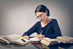 Study. Young woman studying with many books royalty free stock image
