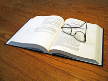 Study. A book open with reading glasses placed on it Royalty Free Stock Images