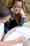 Study. Two young black african college students friends study a book together outdoors Royalty Free Stock Images