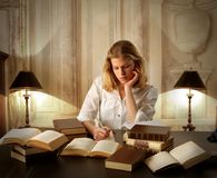 Study. Portrait of a young female student writing on paper and reading books in an ancient interior royalty free stock photo