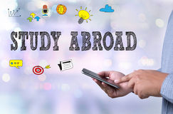 STUDY ABROAD. Person holding a smartphone on blurred cityscape background Royalty Free Stock Photos