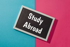 Study Abroad - text on chalkboard. On blue and pink bright background Stock Image