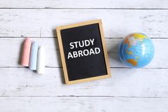 Study abroad. Top view of globe of world map,chalk and blackboard written with & x27; STUDY ABROAD& x27; on white wooden background Stock Photo