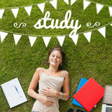 Study against pretty student lying on grass Stock Image