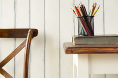 Study. Back to school. A chair, a table, a book and some pencils Stock Photos