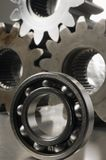 Study of ball-bearing against gears backdrop. Large ball-bearing and gear-wheels royalty free stock photography