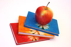Study books and apple. Colorful books and an apple for healthy studying stock photo