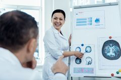 Positive woman presenting her neurology research. Study brain waves. Cheerful asian women presenting her research on neurology to her colleague royalty free stock photos