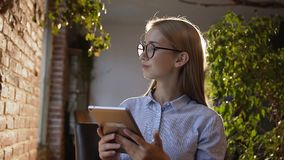 Study, business, people, finance and accounting concept. Beautiful young girl with long hair in glasses works on the. Tablet holding tablet in hand. Young stock video footage