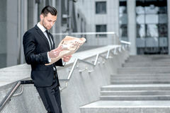 Study competitors. Side view of a young bearded businessman read Royalty Free Stock Images