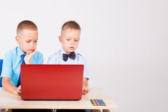 Study on the computer two boys at school stock photos