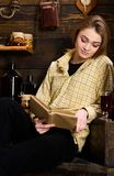 Study concept. Girl student study with book in house of gamekeeper. Girl in casual outfit sits with book in wooden. Vintage interior. Lady on calm face in plaid stock photo