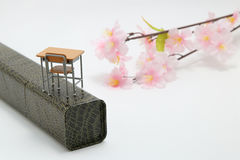 Study desk, diploma, and cherry blossoms on white background. Stock Image