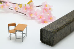 Study desk, diploma, and cherry blossoms on white background. Royalty Free Stock Image