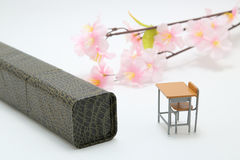 Study desk, diploma, and cherry blossoms on white background. Royalty Free Stock Photography